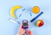 Diabetická glukometr v rukou blízko Inzulínová pera s banán, jablko a sklenici ovocné šťávy