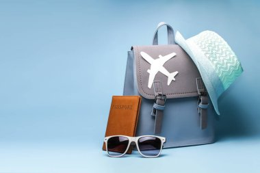 Female hipster tourist backpack with passport and hat on blue background
