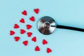 Fotografie Prášky v podobě srdce a stetoskop na modrém pozadí