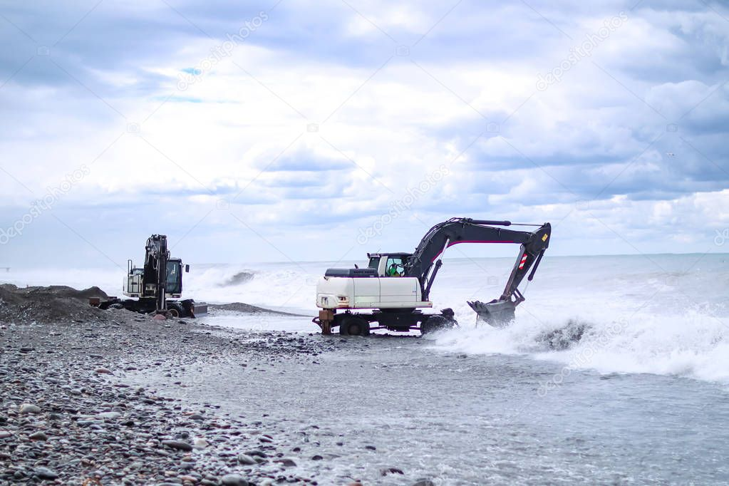 The work of the excavator on the beach at sea