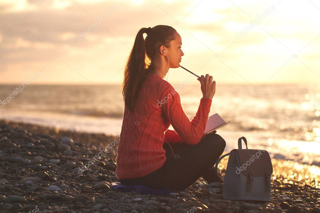 A young, happy woman listening to music and writes her thoughts in a personal diary on the beach at sunset. Enjoy your time and moments. Travel and relaxation