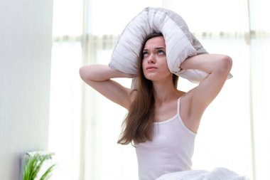 Young woman suffering and disturbed by noisy neighbors and cover