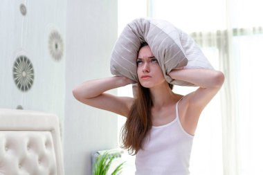 Angry woman suffering and disturbed by noisy neighbors and cover