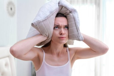 Angry woman disturbed by noisy neighbors and covering her ears w
