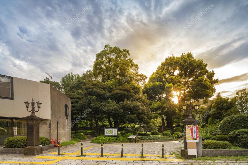 Sunset sky on the entrance of the Hibiya Park ( Hibiya Ken) in Chiyoda City of Tokyo in Japan. Its entrance is decorated with Gothic cast iron lanterns from the 1930s. The poster on the right pillar informs about the Obon Festival.