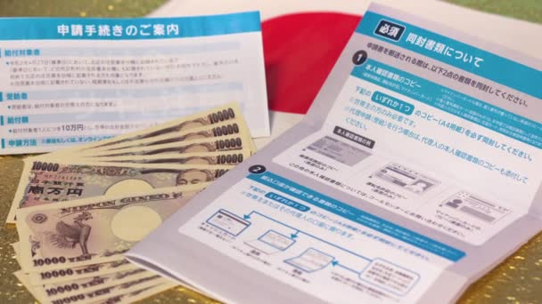 Tracking pan video of Bank notes and 100000 yen benefit sent by the Japanese govt.