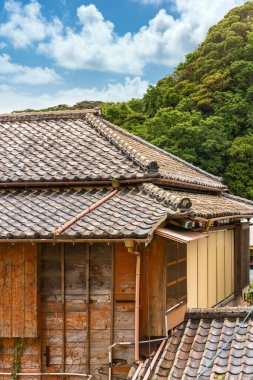 Close-up on a hip roof named yosemunezukuri ornate with decorative Onigawara tile at the end of the ridge and wooden facade named sasarako-shitami of a old traditional Japanese ryokan guesthouse.