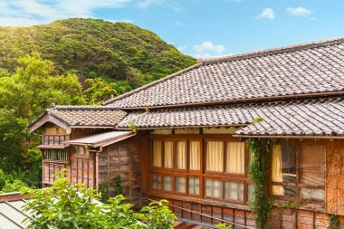 chiba, japan - july 18 2020: Traditional japanese Yosemunezukuri hip roof and sasarako-shitami wooden facade covered with climbing plants on the Kajiya ryokan guesthouse at the foot of Mount Nokogiri.