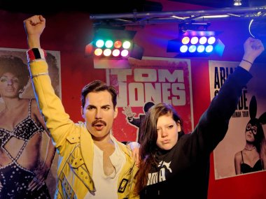 BLACKPOOL, JANUARY 14: Madame Tussauds, UK 2018. Wax statue of Freddie Mercury, best known as the lead vocalist of the rock band Queen and a posing girl, both with raised hands.