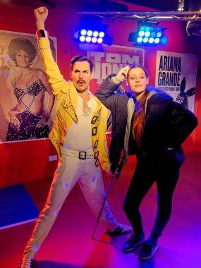 BLACKPOOL, JANUARY 14: Madame Tussauds, UK 2018. Wax statue of Freddie Mercury with a posing girl.