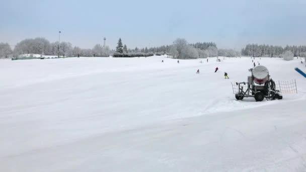 Lidé, sjezdové lyžování na svahu sněhu v zimní lyžařské středisko. Sněhové dělo na lyžařské hory u dětí a dospělých sjezdovka. Zimní aktivity s lyžaři na sjezdovce na zimní den