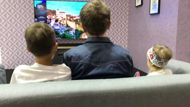 Brno, Česká republika - 10/20/2018: Datart Expo. Otec, syn teenager a malá dcerka dívat se na televizi, sedí na pohovce. Volba Tv rodina nachází. Rodiče s dětmi se jeví program video doma. Redakční shot.