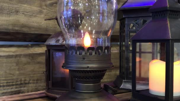 Glowing Christmas lantern in a wooden place with other lamps and candle in background. Indoors New Year decoration: retro rustic oil lamp with burning bright electrical lamp wick. Old fashioned Xmas kerosene lantern with fire light