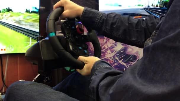 Brno, Česká republika - 10/20/2018: hráč hrát závodní hra na simulátoru s velkou obrazovkou. Volant z herní konzole s rukama za volantem miniaplikace. Počítač závod na Playstation s auto simulátor a křeslo. Několik redakční snímky.