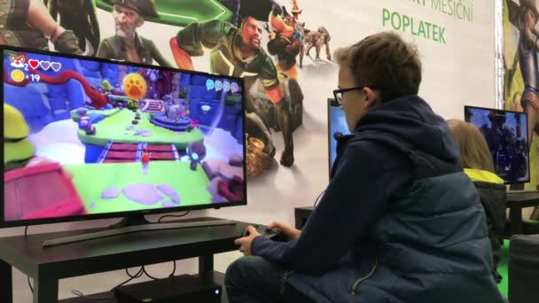 Brno, Česká republika - 11/10/2018: dítě hrát hry Xbox v herní části rodinnou oslavou života! Mladý hráč hraje na velkých obrazovkách. Dítě si užívat video herní konzole v akci pro teenagery. Úvodník