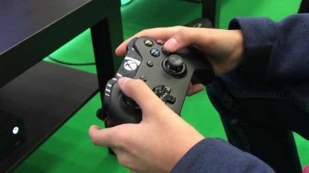 Brno, Česká republika - 11/10/2018: mladé ruce dotýkají tlačítek a drží na herní konzole. Dospívající hrát s ovladačem pro Xbox. Hráč si užívat video hry. Děti herní závislost. Dva výstřely. Úvodník