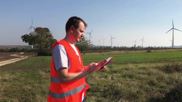 Strojní inženýr v bezpečnostní vesta poznámky v tabletu a díval se na Větrná turbína věží s rotující nože v oblasti větrné slunného dne. Technika práce s barva citlivý tablet a a zadávání dat v projektu rozhraní