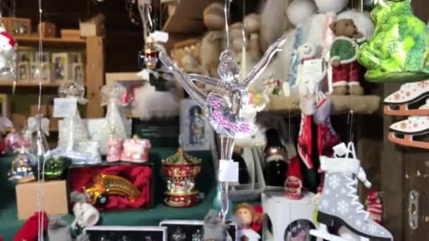 Balletttänzerdekoration hängt am Faden auf dem Weihnachtsmarkt. Christbaumschmuck, der sich am Schaufenster auf Saiten dreht. Weihnachten im Geschäft. Neujahrsbaumschmuck steht bereit. Vorbereitung auf Weihnachtsbaum anziehen