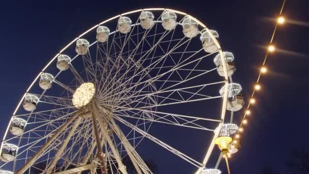 Das drehende Riesenrad im Abendlicht auf dem Weihnachtsmarkt auf dem Festplatz, dunkelblauer Himmel. Tiefstschuss. Karnevalsfahrt auf dem Aussichtsrad beim Neujahrsverkauf. Vergnügungsfahrt auf rotierendem Panoramarad in Lichtern am Markt