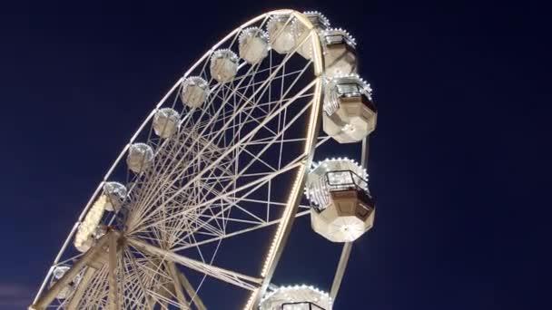 Otočné ruské kolo s lidmi, k nepoznání v večerní osvětlení na vánoční slavnost v výstaviště od dolní pravý, tmavě modré oblohy. Carnival ride na pozorování kolo v novém roce prodeje. Zábavní jízdu na rotační panoramatickou kolo
