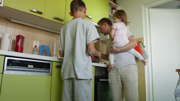 Apák napja. Főzés apa kicsi lánya gazdaság fegyverek segít fia a tanulságokat. Apa egy étkezést, ügyelve a kis-lány és bírálja a tanulás idősebb fiú. 2 gyermek azt állítják a szülő figyelmét. Felnőtt és testvérek haza otthon együtt