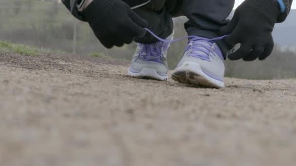 Corridore dellatleta maschio in abbigliamento sportivo invernale, guanti e fitbit legatura lacci per fare jogging sul percorso in sosta e per finire. Uomo lega i lacci delle scarpe per sprint. Sportsman sta preparando per la formazione. Persona preparazione per fare jogging lungo un sentiero, vicino a piedi allaperto