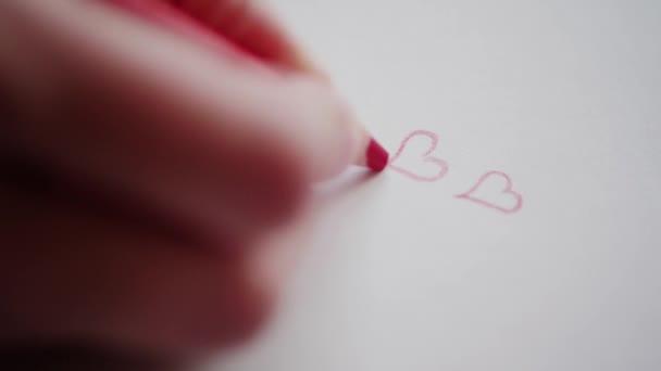 Rechten Hand Zeichnung paar rote Herzen von Bleistift für Schatz am Valentinstag. Gliederung, Herzen Konturen in Liebesbotschaft. Hand konstruiert Valentine Hearts auf handgemachte Karte als romantisches Symbol. Happy Valentinstag. Vorbereitung von Valentine Geschenk für adore