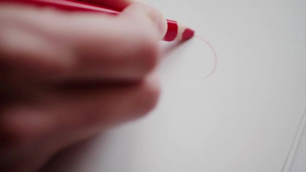 Right hand drawing red heart contour by pencil for sweetheart at Valentines day. Outlining heart in love message. Hand adumbrating Valentine heart on handmade card as romantic symbol. Happy Valentines day. Preparing Valentine gift for adored person