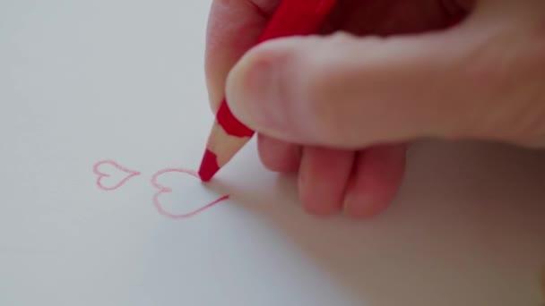 Rechten Hand Zeichnung rote Herzen von Bleistift für Schatz am Valentinstag. Valentine Geschenk für Geliebte Person vorbereiten. Happy Valentinstag. Gliederung, Herzen Konturen in Liebesbotschaft. Hand-konstruiert Valentine Hearts auf handgemachte Karte