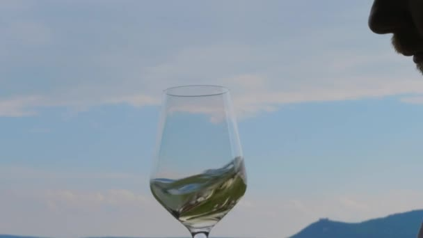 Man swirling, sniffing and tasting white wine in wineglass against blue sky. Person enjoying scent of wine, drinking on vacation. Glass with alcohol in bewhiskered winemaker hand in restaurant. Sommelier, wine producer inspecting quality of wine