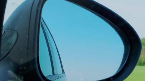 Blue sky and trees reflection in right side rear view mirror during automobile driving on highway. Vacation, weekend concept. Sitter, passenger perspective inside of car. Transportation, transport. Traveling, driver view to black rear view mirror