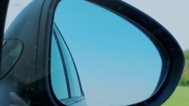 Cielo blu e alberi riflettono nello specchietto retrovisore a destra durante la guida in automobile in autostrada. Vacanza, concetto di fine settimana. Sitter, prospettiva passeggero allinterno dellauto. Trasporti, trasporti. In viaggio, vista del conducente allo specchietto retrovisore nero