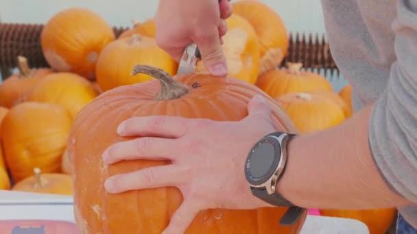 Vyřezávání dýně pro halloweenskou lucernu se strašidelným obrysem obličeje, mužské ruce zastřižené víko, čas vypršel. Vysypává dýni na slavnosti. Osoba připravující výzdobu na večírek. Dospělý krájí dýni nožem. Příprava symbolu podzimní párty