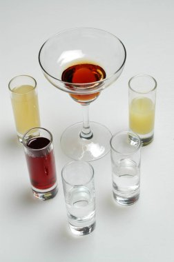 Different colorful alcoholic drinks on gray background
