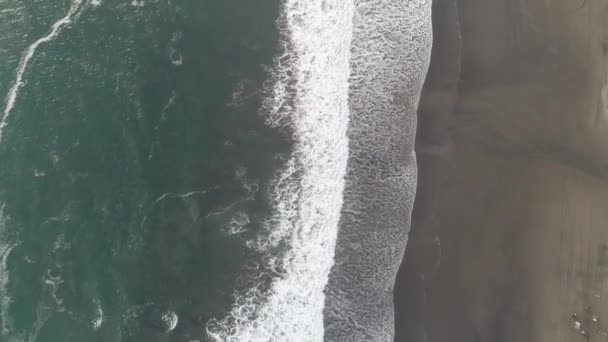 Drone footage of waves lapping at sandy Indonesian shoreline