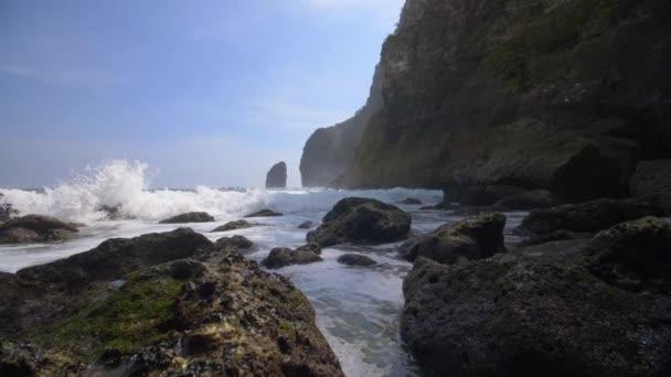Foamy waves breaking over rocks by the Indonesian coastline