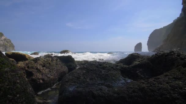 Frothy waves breaking over rocks in an Indonesian bay