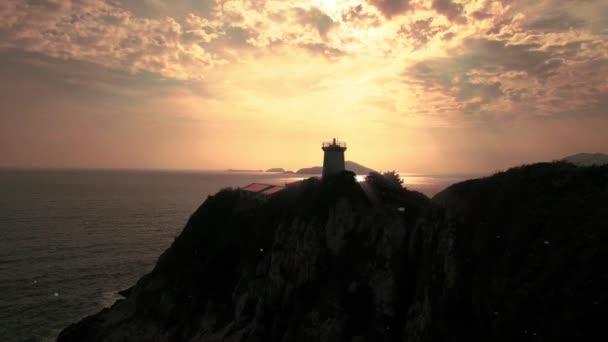 Leuchtturm in Richtung Sonnenuntergang über dem Ozean