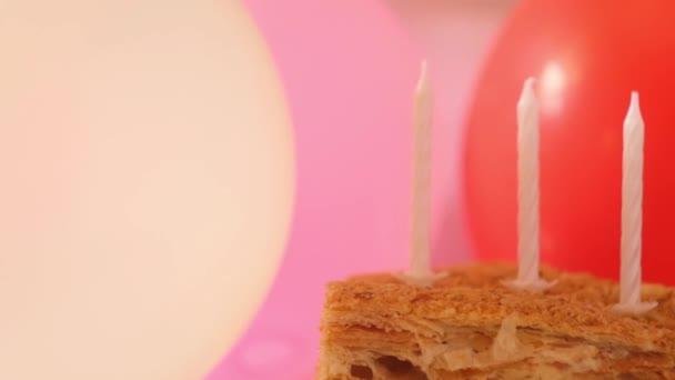 Születésnapi torta gyertyákkal. Piros és rózsaszín lufik a háttérben