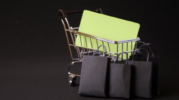 Shopping cart or trolley with paper bags on black background. Credit card mock up. Online store purchases. Black background. Minimalism design. Black friday promotion. Final sale