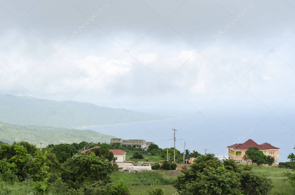 Sky covered with rain clouds, fog and mist hangs across the coastal region of the sea and peninsula. Closer inland, are fresh green trees and grass among residential houses and water tank.