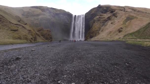 Skogafossův vodopád na jihu Islandu, na zlatém prstenci. Návštěvníci se přišli podívat na vodopád, turisté chodí na úpatí hory.