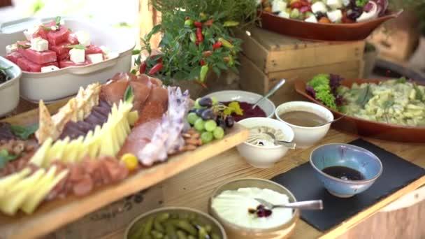 Bufetový stůl se sýrem a krájením klobás, omáčkami, saláty a zeleninovými plátky. Dřevěný stůl v hotelu je all inclusive.