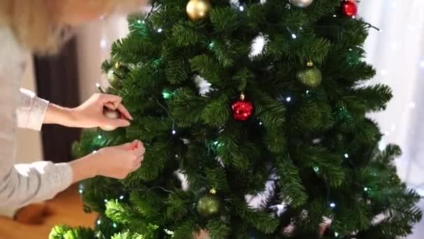 Egy fiatal nő karácsonyi golyókkal dekorál egy bolyhos karácsonyfát a szobában. Gyönyörű fényes karácsonyi háttér. Ünnepi karácsonyi hangulat.