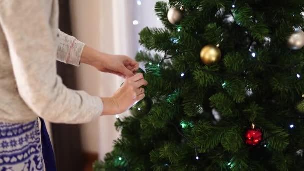 Mladá žena zdobí vánoční koule nadýchaný vánoční stromeček v místnosti. Krásné jasné vánoční pozadí. Slavnostní vánoční nálada.