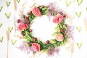 Virágos gyomlálás koszorú készült rózsa és zöld levelek fehér alapon
