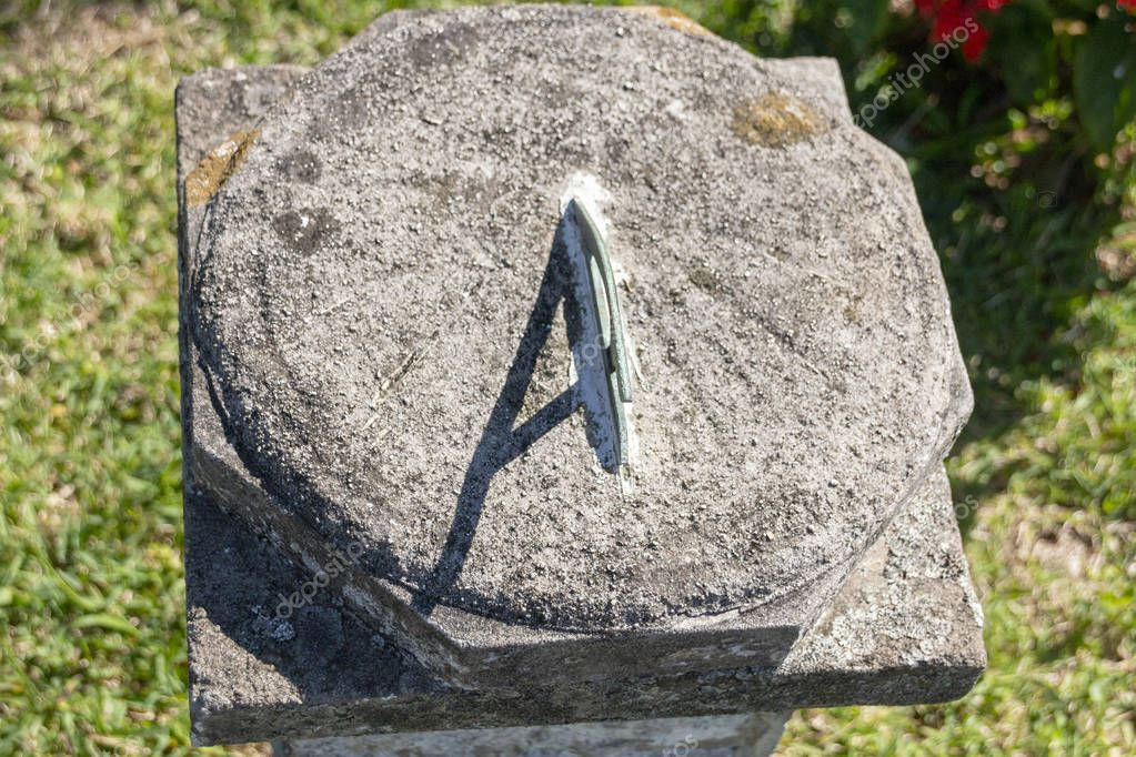 A close up view of a sun dial on a concrete stand in an outside garden
