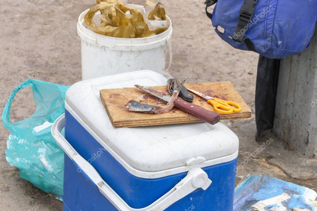 A close up view of a fishermans sardine bait on a wooden board with two knifes, yellow handle scissors that has been cut up and used to catch fish