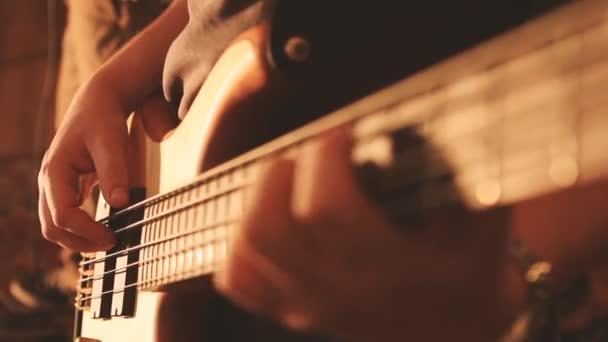 Basový kytarista blízko hrát virtuózní bas s prsty