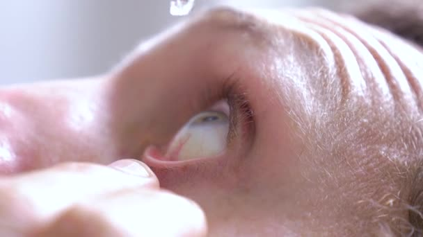 Macro of a man putting eye drops to moisturize and relieve irritation